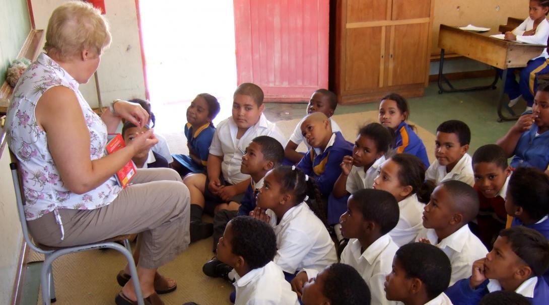 Niños escuchan la clase de inglés de voluntaria de educación.